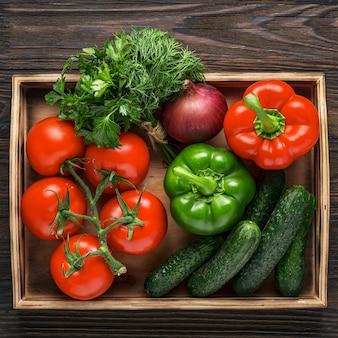 Свежие и сочные овощи в деревянном ящике. ингредиенты овощного салата. огурцы, помидоры, перец, лук, зелень