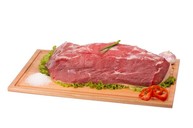 Свежая и сырая говядина на разделочной доске на белом фоне.