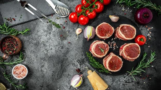 新鮮な生肉。ベーコンに包まれたサーロインメダリオンステーキは、調理の準備ができた古い肉屋で提供されます。バナー、テキストのメニューレシピの場所、上面図。