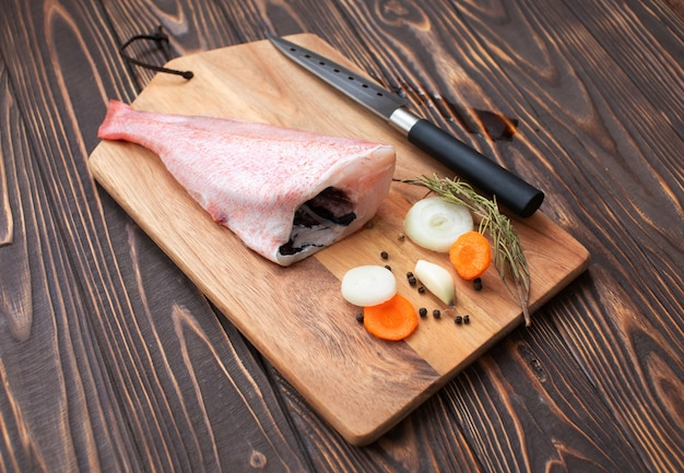 신선 하 고 나무 패드, 선택적 초점에 레몬과 당근 같은 재료로 원시 핑크 퍼 치 물고기를 요리 할 준비가되었습니다.
