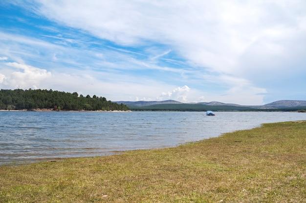 自然に囲まれた大きな川と水の真ん中に小さなヨットがある新鮮で夏の風景。