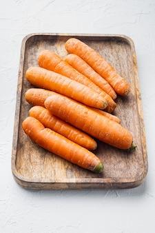 흰색 배경에 나무 쟁반에 신선하고 달콤한 당근 무리 세트