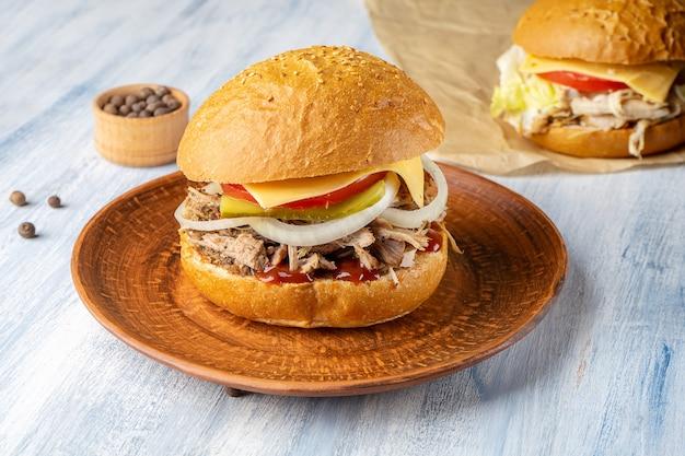 ローストビーフ、タマネギ、青い木製の背景にチーズと新鮮でおいしいハンバーガー。アメリカの伝統的なファーストフード。チーズバーガー、チキンブルガー