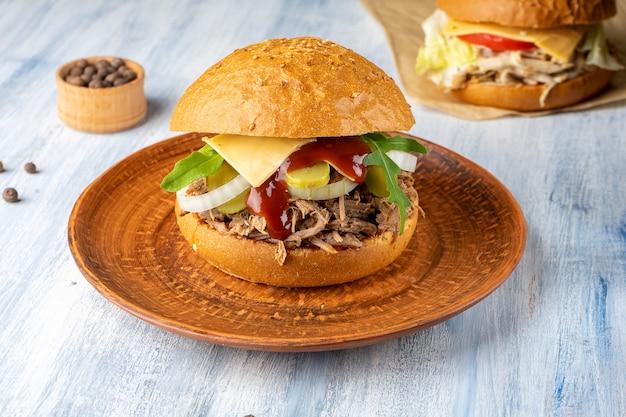 ローストビーフ、タマネギ、アスパラガス、青い木製の背景にチーズと新鮮でおいしいハンバーガー。アメリカの伝統的なファーストフード。チーズバーガー、チキンブルガー