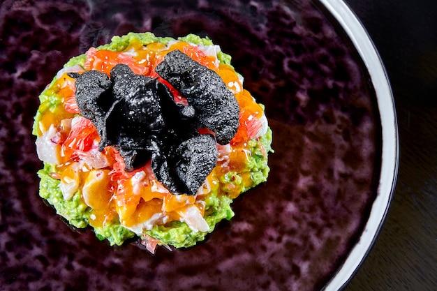 ドラドの新鮮でおいしいセビチェ。生魚のシーフード料理。フィッシュ、ライスチップ、アボカドのセビーチェ。ラテンアメリカ料理。閉じる。高級カジュアルダイニングのコンセプト。セレクティブフォーカス食品背景