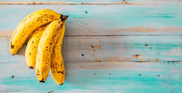 青いトレンディな木製の古いテーブルに新鮮でおいしい天然バナナの果実