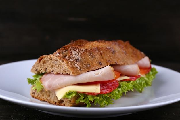 Свежий и вкусный бутерброд с сыром и овощами на тарелке на деревянном