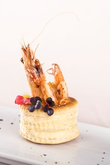 Fresh appetizer with shrimp,  on pastry, decorated with eatable red flower and green leaf