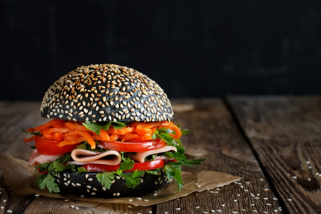 Fresh appetizing bright burger with sesame seeds with fresh vegetables (tomato, bell pepper)