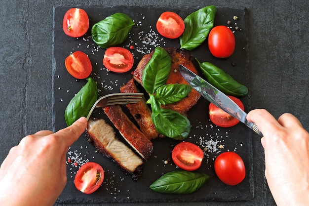 Fresh appetizing meat steak on a board with tomatoes and basil.