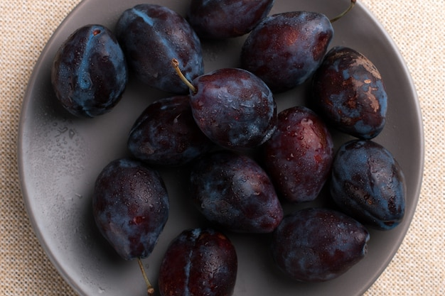 Fresh appetizing plums in a gray bowl, summer , copyspace.