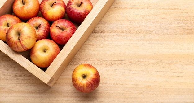 Fresh apple background with copy space. red apples in crate on wooden table