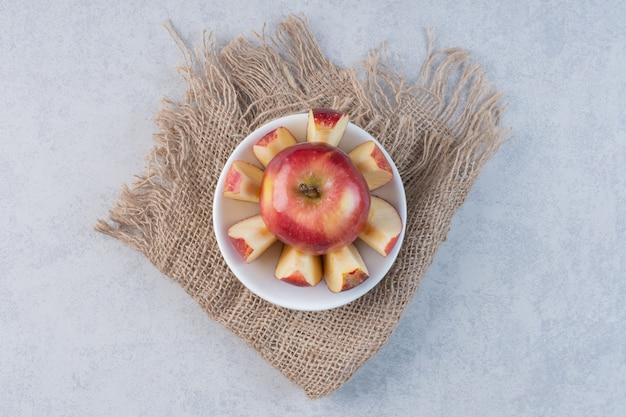 Frutta mela fresca con pezzi interi o tagliati su sfondo grigio.