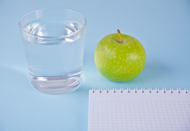 Fresh apple, glass of water and notebook on blue