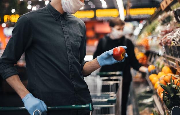Свежее яблоко в руках мужчины в защитных перчатках. гигиена и забота о здоровье