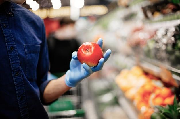 Свежее яблоко в руках мужчины в защитных перчатках.