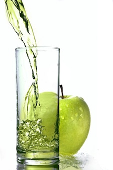 Fresh apple juice in glass with green apple isolated on white