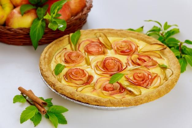 白いテーブルの上にバラと葉のような装飾が施された新鮮なアップルパイ。