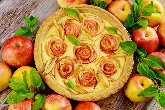木のテーブルの上のバラのような装飾が施された新鮮なアップルパイ。上面図。