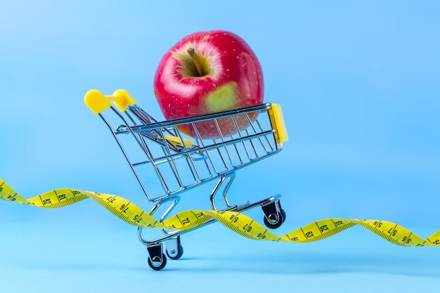 Fresh apple in a shopping cart and measuring tape. diet concept. plan to get in shape, to do sports and lose extra kilograms