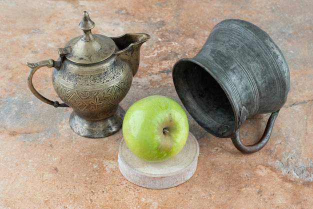 A fresh apple with an ancient cups on marble