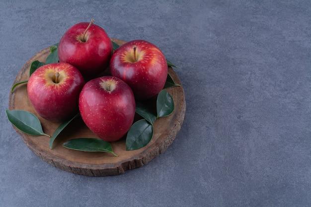 Свежие яблоки и листья на доске на мраморном столе.
