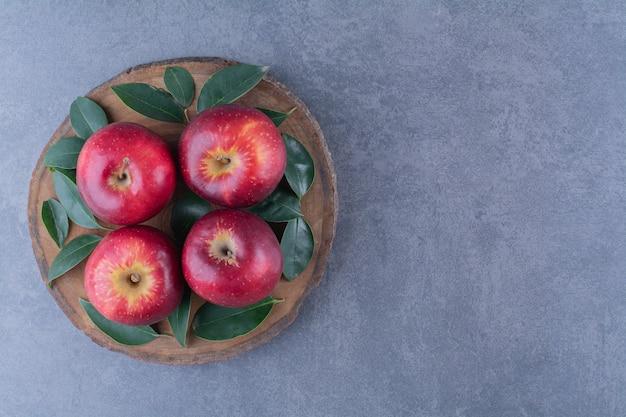 대리석 테이블에 있는 보드에 신선한 사과와 잎.