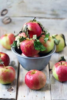 Fresh apples in a bowl on a wooden surface