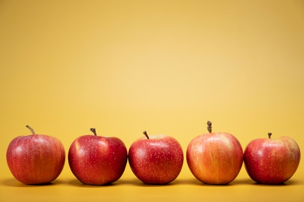 Fresh apples on a bright yellow background in an advertising foodphoto style. horizontal
