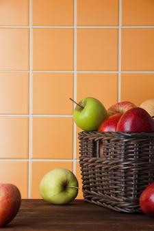 オレンジ色のタイルの背景にバスケットの新鮮なリンゴ。側面図。テキストのためのスペース