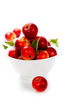 Свежие яблоки в миске над белой