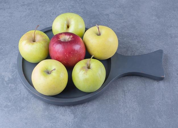 大理石のテーブルの上の鍋に新鮮なリンゴ。