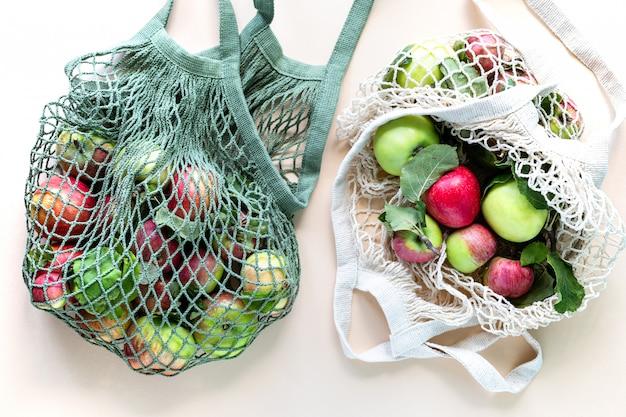 Свежие яблоки в сетке хозяйственной сумки. без отходов, без пластика. здоровое питание и детокс. осенний урожай. плоская планировка, вид сверху.