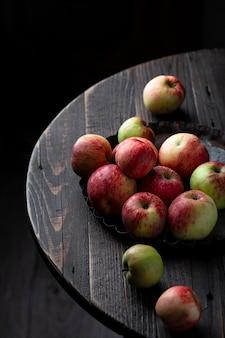 Свежие яблоки в миске на деревянном столе
