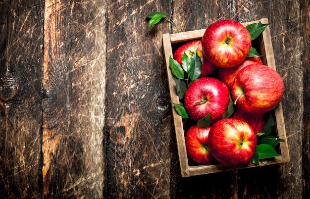 木製のテーブルの上の箱の中の新鮮なリンゴ
