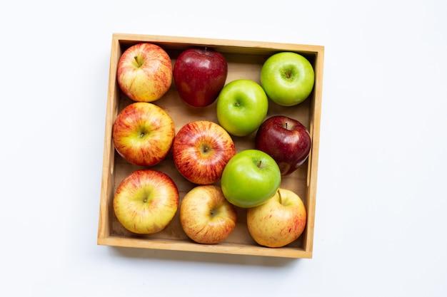 白い表面の木製の箱に新鮮なリンゴ。