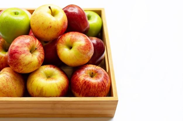 白い壁の木製の箱に新鮮なリンゴ。