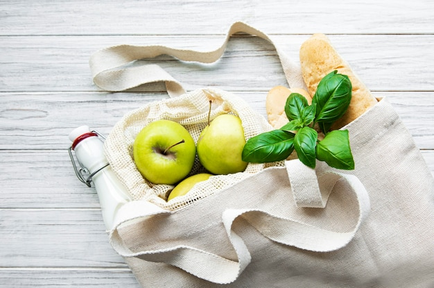 Fresh apples, milk and bread in eco cotton bag on a white wooden table