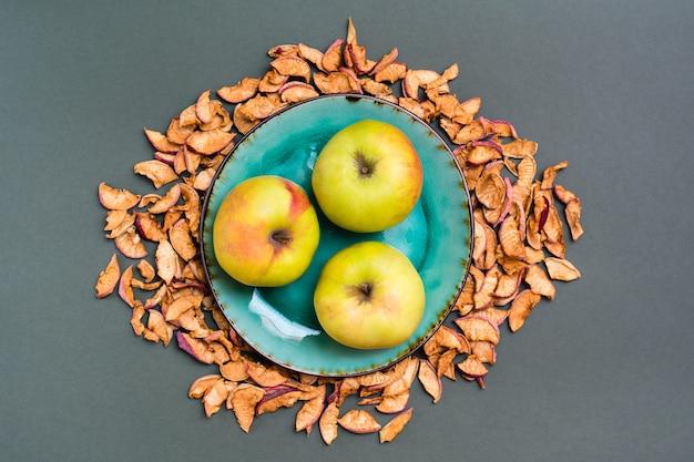 Свежие яблоки на тарелке и кусочки сухих яблок вокруг на зеленом фоне. вид сверху