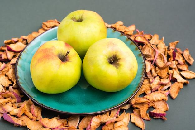 皿の上の新鮮なリンゴと緑の背景の周りの乾燥したリンゴの断片