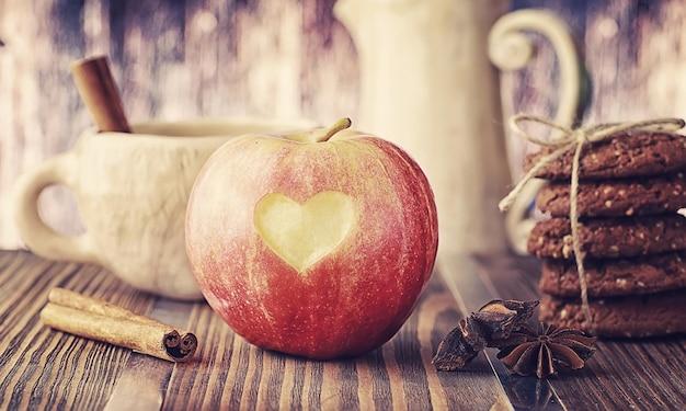 木の板に新鮮なリンゴ。赤いリンゴの収穫。テーブルの上の果物とシナモン。