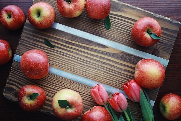 나무 보드에 신선한 사과입니다. 빨간 사과의 수확. 테이블에 과일과 계피입니다.