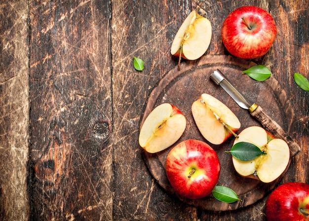 木製のテーブルのまな板に新鮮なリンゴ。