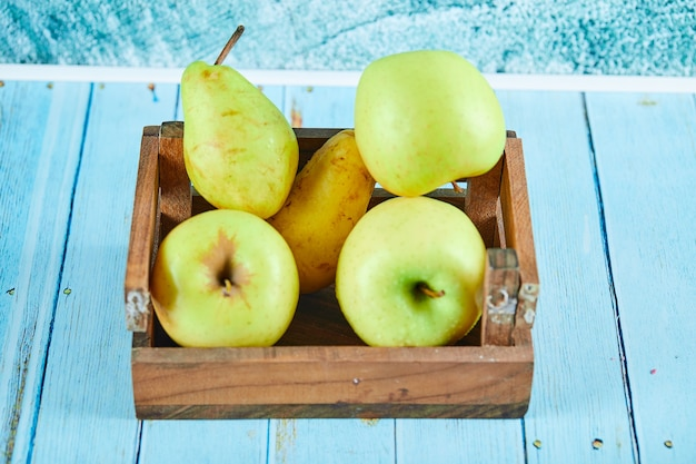 Fresh apples and pears in a wooden box on blue surface.