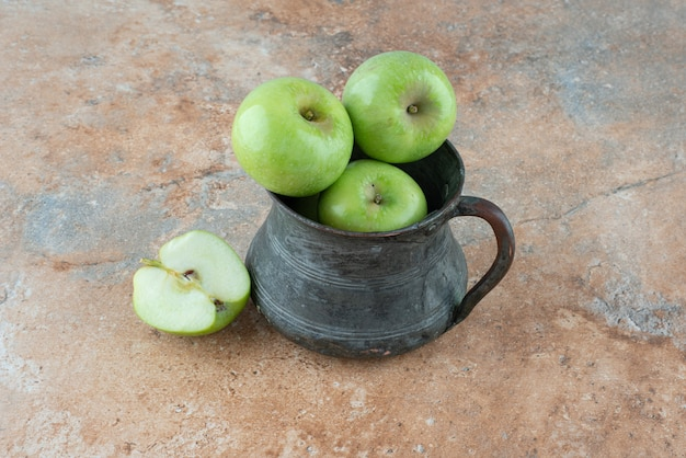 A fresh apples with an ancient cup on marble table.