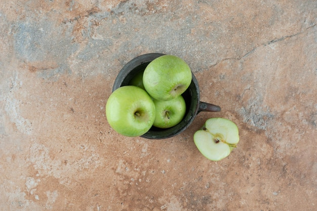A fresh apples with an ancient cup on marble