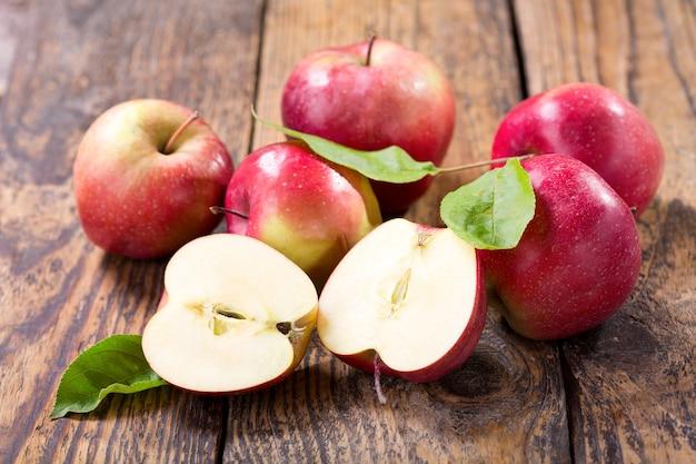 나무 테이블에 잎을 가진 신선한 사과