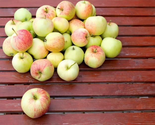 木製のテーブルの上に、素朴なスタイルの新鮮なリンゴ。