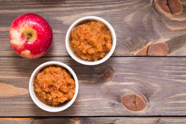 Fresh applesauce in bowls and red apples on a wooden table. copyspace