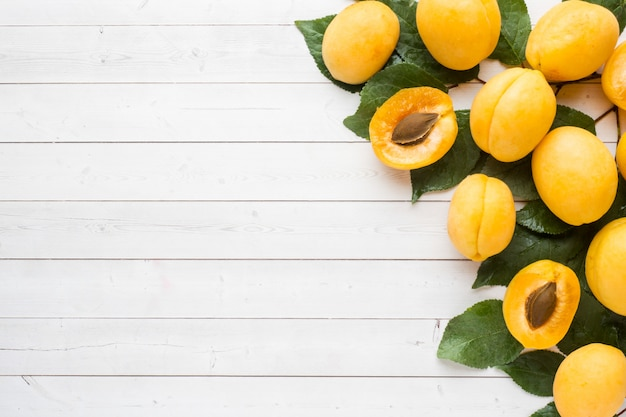 Fresh apricot berries with leaves on a light table. background copyspace